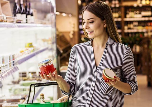A woman in the supermarket studies a candle made with sustainable palm oil.