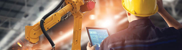 engineer in factory with tablet looking at robot arm