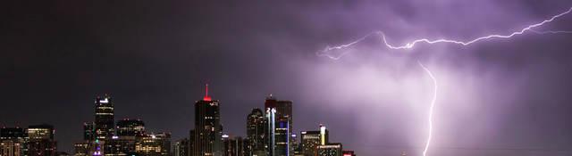 Nighttime skyline with lightning striking a building