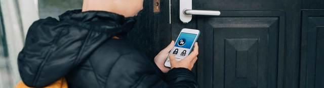 Boy unlocking home with smart phone