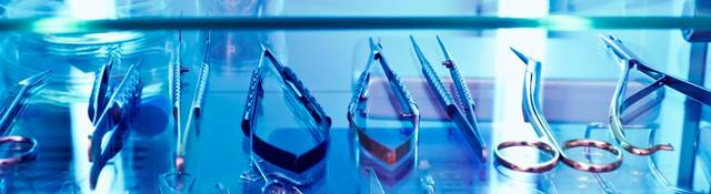 An array of medical devices sit within a cabinet basking in UV light.