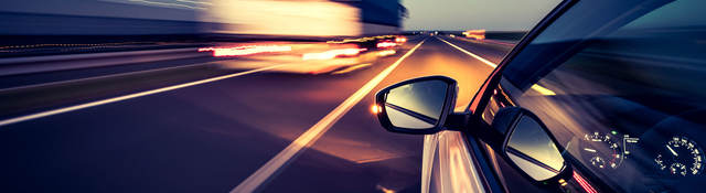 Silver car with side-view mirror driving on highway beside heavy duty truck at night