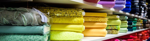 Colorful textiles folded on shelves