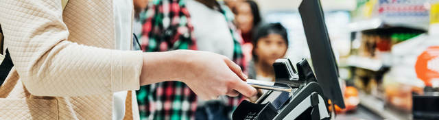 woman using a mobile phone to pay for groceries