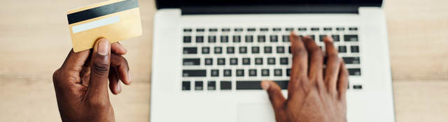 man looking at a credit card and typing on laptop keyboard
