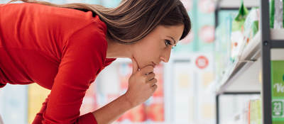 young woman choosing private label products at store