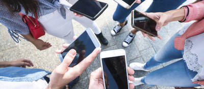 A group of young adults scrolling through their cell phones.