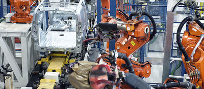 Vehicle factory manufacturing with robotic arms and automation.