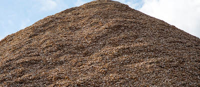 Pile of mulch woodchips against a blue sky
