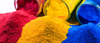 Magenta, yellow and cyan powders spill out of glass jars next to each other.
