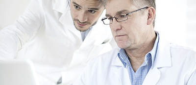 Two men in lab coats looking at a laptop.
