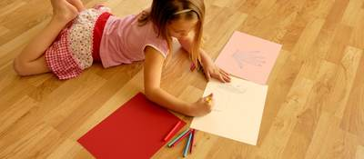 Girl coloring on a wood floor