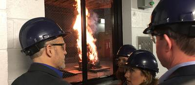 Four members of the JCI Fire Suppression team observe their antifreeze product in action at UL laboratories. An undetermined object is on fire and the team is looking through a window at the event.