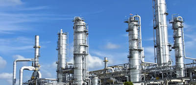 Energy processing facility against a blue sky with drifting clouds