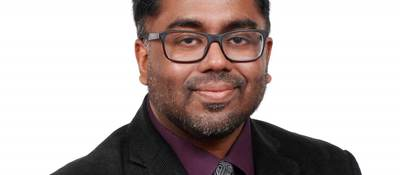 Anura Fernando wears a black jacket, burgundy shirt and grey tie for his corporate picture.