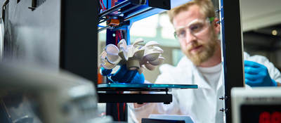 Photo of a scientist testing 3D printed plastic object
