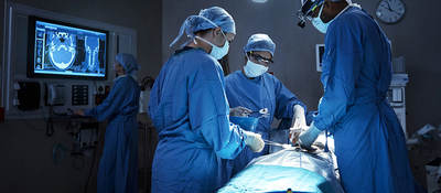 Surgeons with  a patient in an operating room