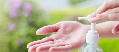 Female hand dispensing hand sanitizer onto open palm