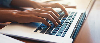 Photo of a person typing on a laptop