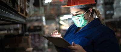 Portrait of mid adult woman wearing face mask using digital tablet - working at warehouse/industry.