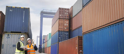 Two workers wearing a high visibility vest inspecting a shipping dock