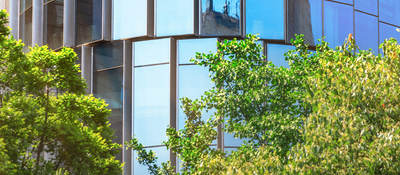 glass building  with trees in front of it