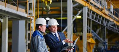 Two men in warehouse looking at laptop