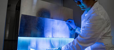A woman uses UV light to inactivate harmful material on products.