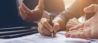 Photo of a person signing a contract