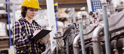 female engineer inspects industrial equipment