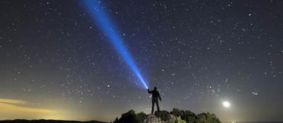Flashlight illuminating a starry sky
