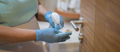 Employee spraying disinfectant on cloth to sanitize door handle