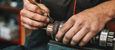 Manual worker repairing electric motor in a workshop