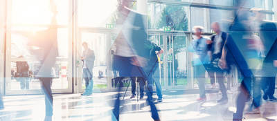Business people walking in the lobby of a building with glass windows
