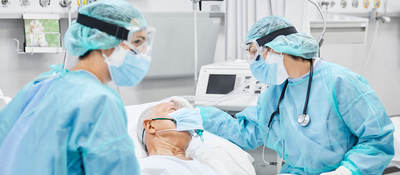 Medical professionals wearing personal protection equipment (PPE) attending to a hospital patient