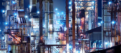 A brightly lit commercial oil refinery is shown at night.