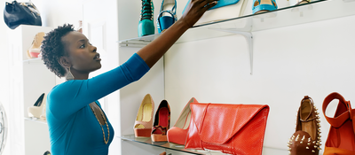 Woman reaching for a purse on a retail shelf