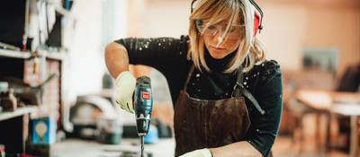 Female carpenter using power tool