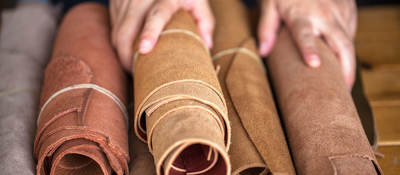 A pair of hands holds rolled leather sheets