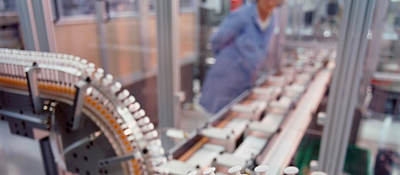 A syringe factory with a worker in the background