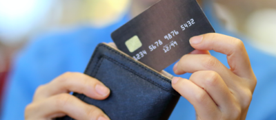 Woman pulling a credit card out of a wallet