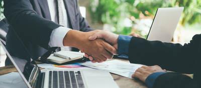 Business people shaking hands across a desk