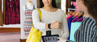 woman paying with smartwatch in store