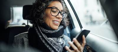 woman looking at a mobile phone in car