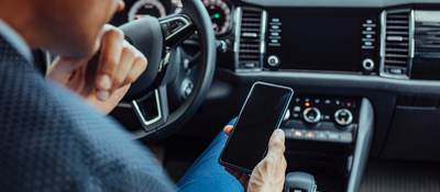 man looking at a mobile phone in car