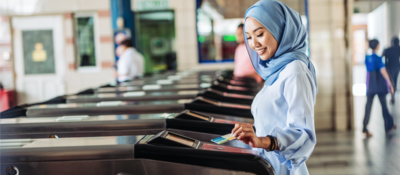woman tapping a card on the ticket gate