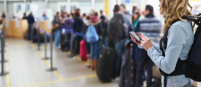 Person using cellphone in line at the airport