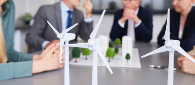 Scale models of wind turbines on a desk during a planning meeting