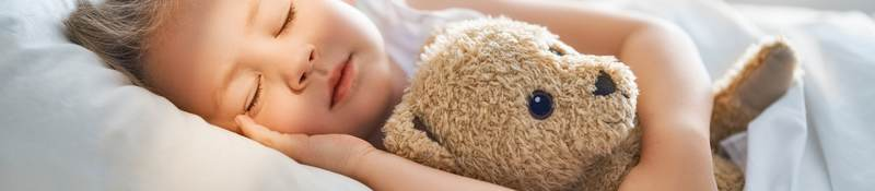 photo of a child sleeping with a stuffed toy