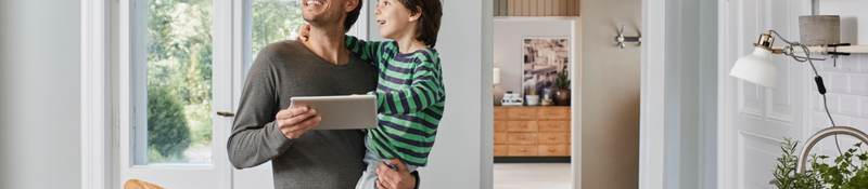 Father and son switching on smart lighting in the kitchen